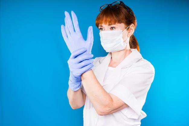 Die krankenschwester zieht medizinische handschuhe an und wird den eingriff mit dem patienten durchführen