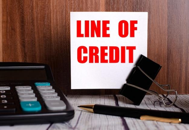 Die kreditlinie steht auf einer weißen karte auf einer holzoberfläche neben einem taschenrechner und einem stift