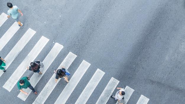 Die kreuzansicht von oben geht von den leuten auf die fußgängerzone in der stadtstraße, vogelperspektive