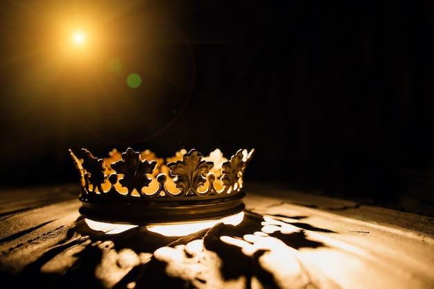 Die krone auf schwarzem hintergrund wird von einem goldenen strahl beleuchtet battle for the throne