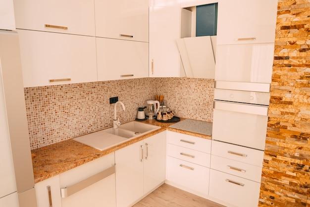 Die küche in der wohnung. das design des küchenzimmers. holzküche, kühlschrank, herd, esstisch. kücheninterier.