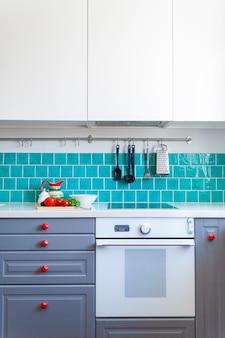 Die küche verfügt über dunkelgraue schränke mit flacher front, weiße quarzarbeitsplatten und eine glänzend blaue pflegekachel.