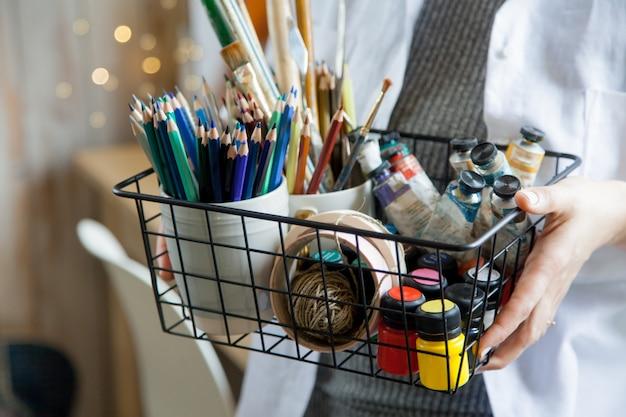Die künstlerin sitzt an ihrem arbeitsplatz und malt porträts in aquarellfarben. fertige arbeiten hängen an der wand. sie hat eine graue katze im arm.
