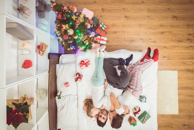 Die küssende familie lag mit geschenken auf dem bett. von oben betrachten