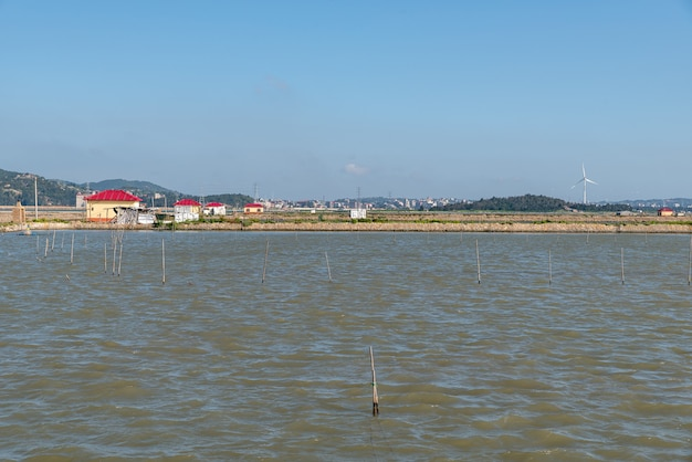 Die küste unter blauem himmel, dem meer gegenüber sind berge und windkraft