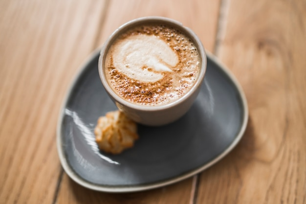Die kunst des cappuccinos auf keramischer schale mit plätzchen über dem holztisch