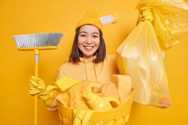 Die lächelnde asiatische frau trägt werkzeuge zum fegen des bodens, der über gelber wand isoliert wird