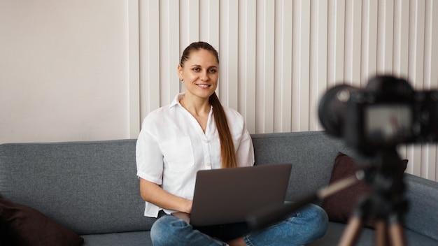 Die lächelnde bloggerin nimmt ein neues video auf. sie sitzt zu hause auf der couch und hält einen laptop in der hand. positives business-blog-konzept.