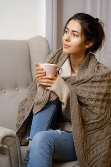 Die lächelnde dame in schicker, trendiger kleidung sitzt mit einer tasse tee auf dem sessel.
