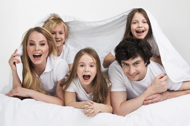 Die lächelnde familie mit drei kindern wacht im bett auf