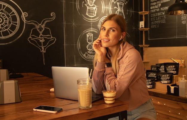 Die lächelnde frau benutzt einen laptop, sitzt im café mit einer tasse cappuccino und einem dessert