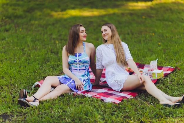 Die lächelnde frau, die draußen eine entspannende mittagspause hat, sitzt im gras und isst.