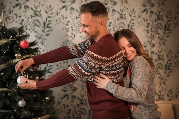 Die lächelnde frau, die mann von der rückseite in den strickjacken umarmt, nähern sich weihnachtsbaum