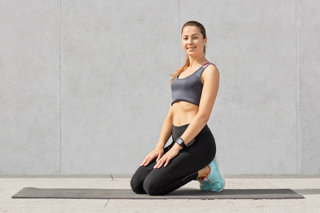 Die lächelnde frau, die nach dem knirschen auf der fitnessmatte in einem guten mod ist, steht auf den knien, trägt sportbekleidung und hat einen gesunden körper