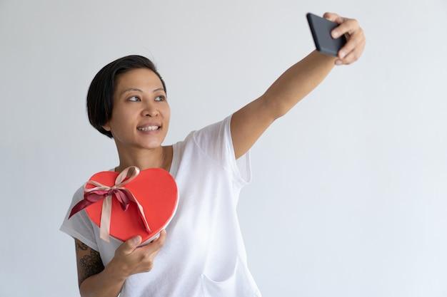 Die lächelnde frau, die selfie foto mit herzen macht, formte geschenkbox