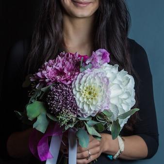 Die lächelnde frau, die weiß und purpur hält, färbte mischungsblumenblumenstrauß