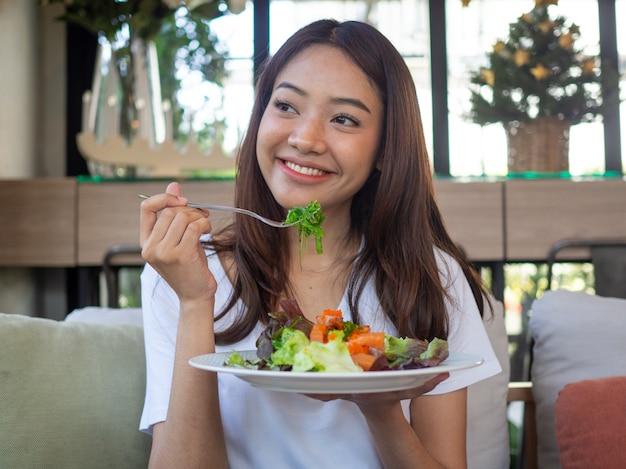 Die lächelnde frau genießt es, einen lachssalat zu essen.