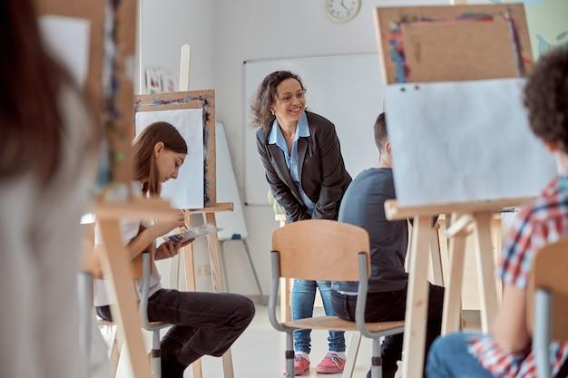 Die lächelnde glückliche lehrerin gemischter rassen schaut auf die zeichenarbeit eines schülers
