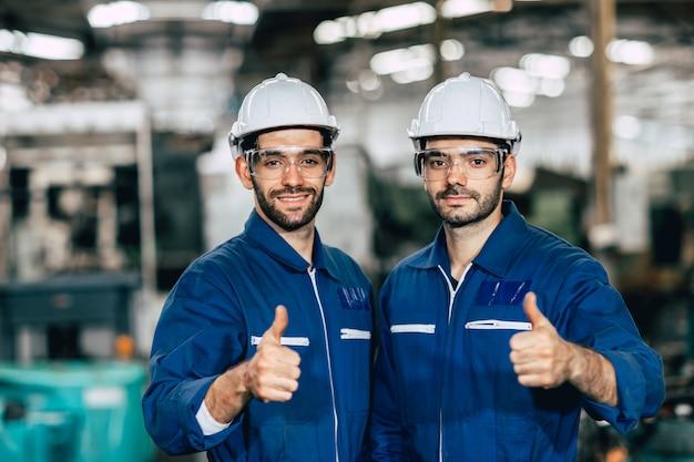 Die lächelnde hand des glücklichen arbeiterteams zeigt daumen für gutes arbeiten in der fabrik.