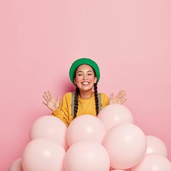 Die lächelnde hübsche asiatische dame hält die handflächen in der nähe von heliumballons hoch, ist in hochstimmung, trägt eine grüne baskenmütze und einen gelben freizeitpullover und schmückt den raum für besondere anlässe