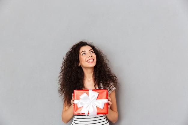 Die lächelnde hübsche frau, die geschenk hält, wickelte kastengefühlsvergnügen ein, um geschenk auf sylvesterabend zu empfangen