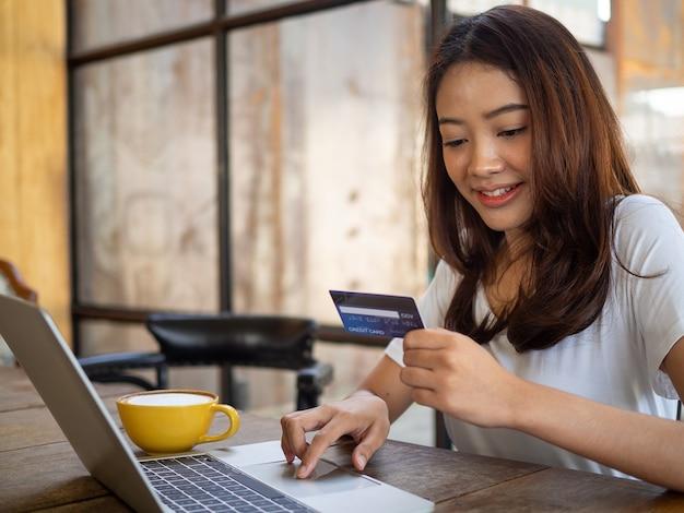 Die lächelnde junge asiatin genießt es, am computer online einzukaufen und mit kreditkarte online zu bezahlen. bequemes geld ausgeben. bleib sicher, shoppen von zu hause und soziale distanz