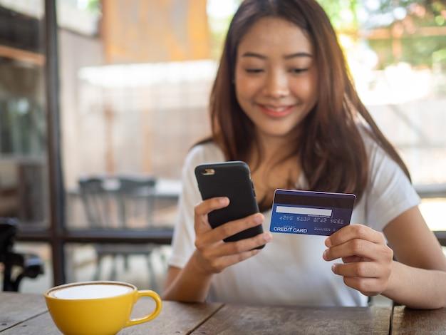 Die lächelnde junge asiatin genießt es, mit dem smartphone online einzukaufen und mit kreditkarte online zu bezahlen. bequemes geld ausgeben. bleib sicher, shoppen von zu hause und soziale distanz