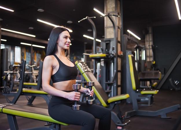 Die lächelnde junge frau hält hanteln in den händen, während sie auf einer bank im fitnessstudio sitzt