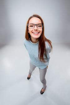 Die lächelnde junge geschäftsfrau auf grauer wand