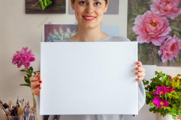 Die lächelnde junge künstlerin hält eine leere weiße leinwand in ihren händen vor dem hintergrund eines gemütlichen arbeitsplatzes mit gemälden an der wand und werkzeugen. platz für werbung