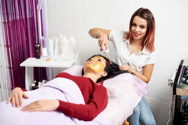 Die lächelnde kosmetikerin führt das verfahren der mikrostromtherapie am haar einer schönen jungen frau in einem schönheitssalon durch.