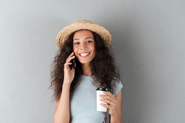 Die lächelnde lockige frau der schönheit im hut, die durch das smartphone mit kaffee in der hand spricht