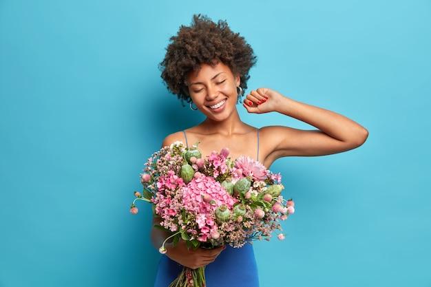 Die lächelnde sorglose afroamerikanerin mit den lockigen haaren feiert die posen des 8. märz mit einem schönen blumenstrauß und trägt ein festliches kleid, das über der blauen wand isoliert ist