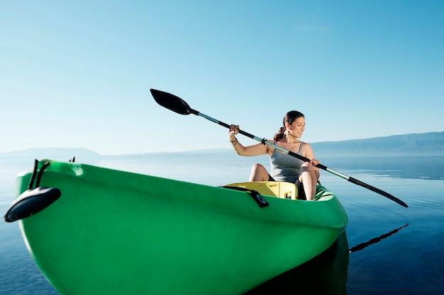 Die lächelnde sportlerin sitzt in einem kajak mit paddeln in der hand im meer gegen den blauen himmel.