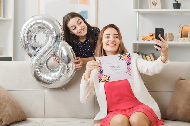Die lächelnde tochter, die hinter dem sofa steht und die ballonmutter mit der nummer acht hält, mit der grußkarte auf dem sofa sitzend, macht ein selfie am glücklichen frauentag im wohnzimmer