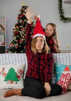 Die lächelnde tochter setzt die weihnachtsmütze auf den kopf der mutter und hebt die hand, sitzt auf der couch und genießt die weihnachtszeit zu hause