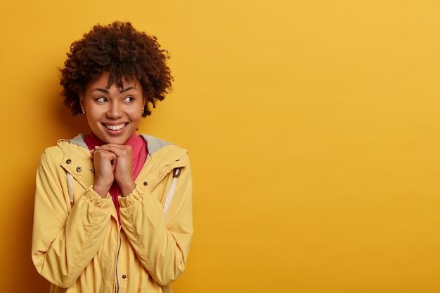 Die lächelnde zarte junge frau hält die hände unter dem kinn, schaut mit einem breiten lächeln zur seite, trägt einen lässigen anorak, träumt von etwas angenehmem, posiert an der gelben wand, leerer raum