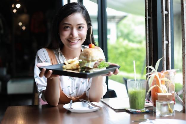 Die lächelnden und glücklichen asiatinnen und genossen, hamburger am kaffee und am restaurant zu essen, entspannen an sich zeit