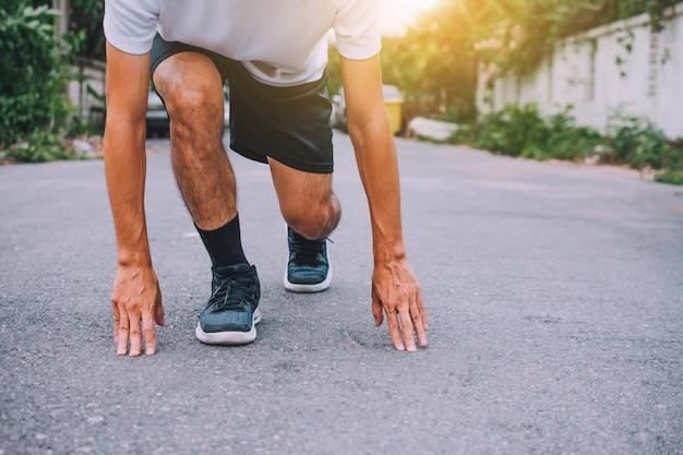 Die läufer, die in den schuhen gebunden werden, der mann, der auf der straße laufen, laufen für übung, laufsporthintergrund und nahaufnahme am laufschuh