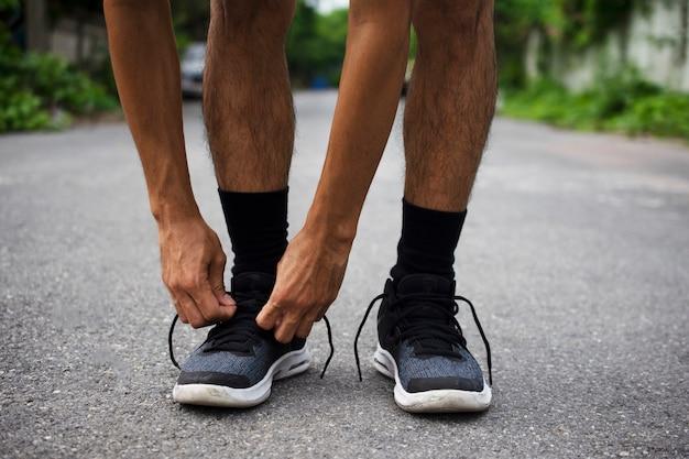 Die läufer, die in den schuhen gebunden werden, mann, der auf der straße laufen, laufen für übung