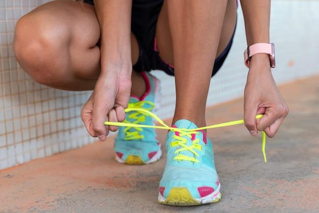 Die läuferin bindet ihre schuhe, bevor sie rennt