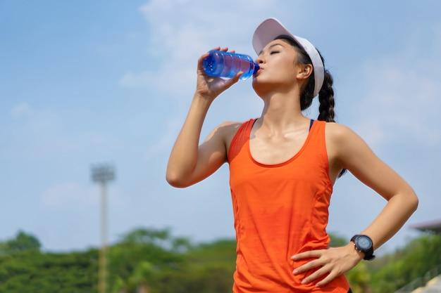 Die läuferin trinkt nach dem training wasser