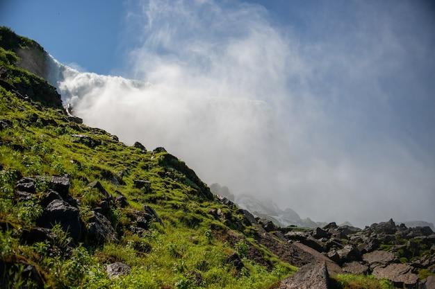 Die landschaft der mit moos bedeckten felsen mit dem niagara fällt unter das sonnenlicht