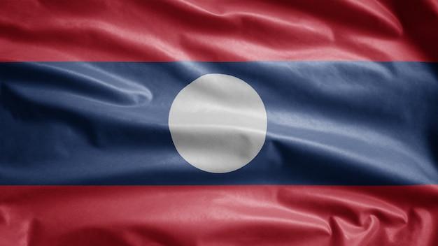 Die laotische flagge weht im wind. nahaufnahme von laos banner weht, weiche und glatte seide. stoff textur fähnrich hintergrund. verwenden sie es für das konzept für nationalfeiertage und länderanlässe.