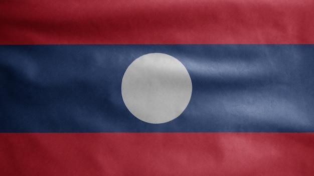 Die laotische flagge weht im wind. nahaufnahme von laos banner weht, weiche und glatte seide. stoff textur fähnrich hintergrund.