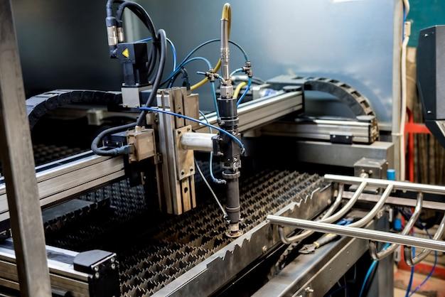 Die laserschneidmaschine schneidet die löcher in rohren.