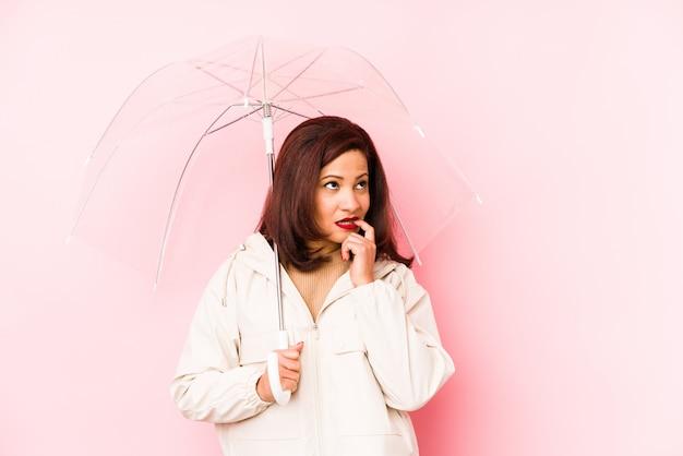 Die lateinische frau des mittelalters, die einen regenschirm trägt, lokalisierte das entspannte denken an etwas, das einen kopienraum betrachtet.