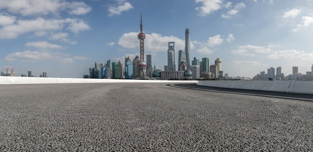 Die leere asphaltstraße wird entlang moderner geschäftsgebäude in chinas städten gebaut.