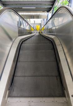Die leere moderne rolltreppe, die im s-bahnhof noch nicht in betrieb ist, geht nach unten zur bushaltestelle., vorderansicht mit dem kopierraum.