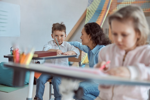 Die lehrerin erklärt den grammatikregeln der kleinen männlichen schüler